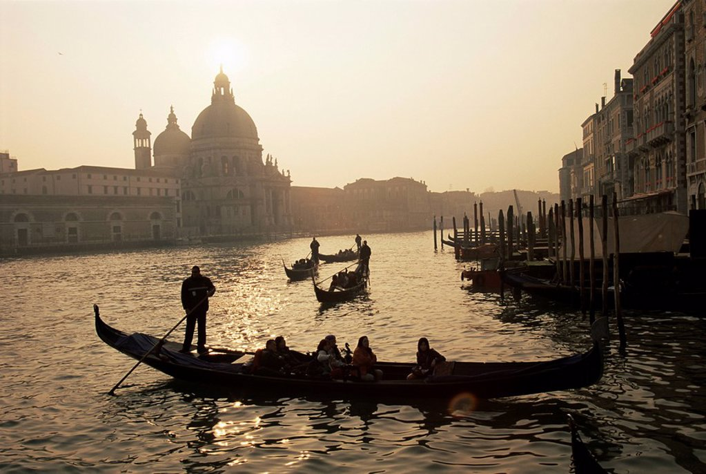 Sunset view along the Grand Canal to Santa Maria Della Salute church with gondoliers in silhouette, Venice, Veneto, Italy, Europe : Stock Photo
