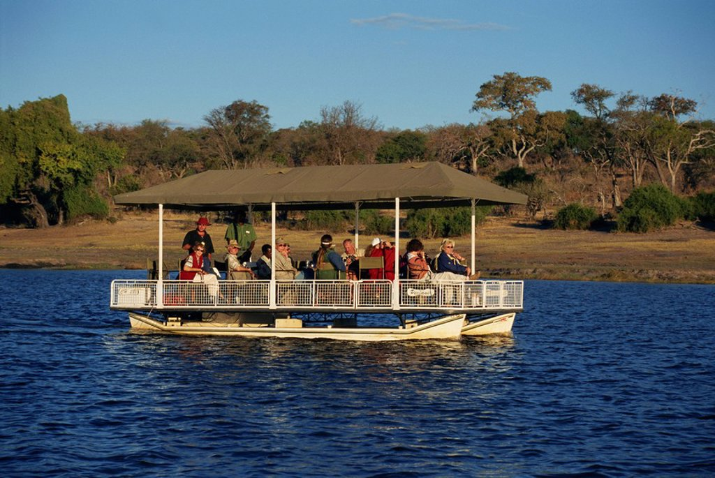 Tourists game viewing on boat on the Chobe River, Chobe National Park, Botswana, Africa : Stock Photo