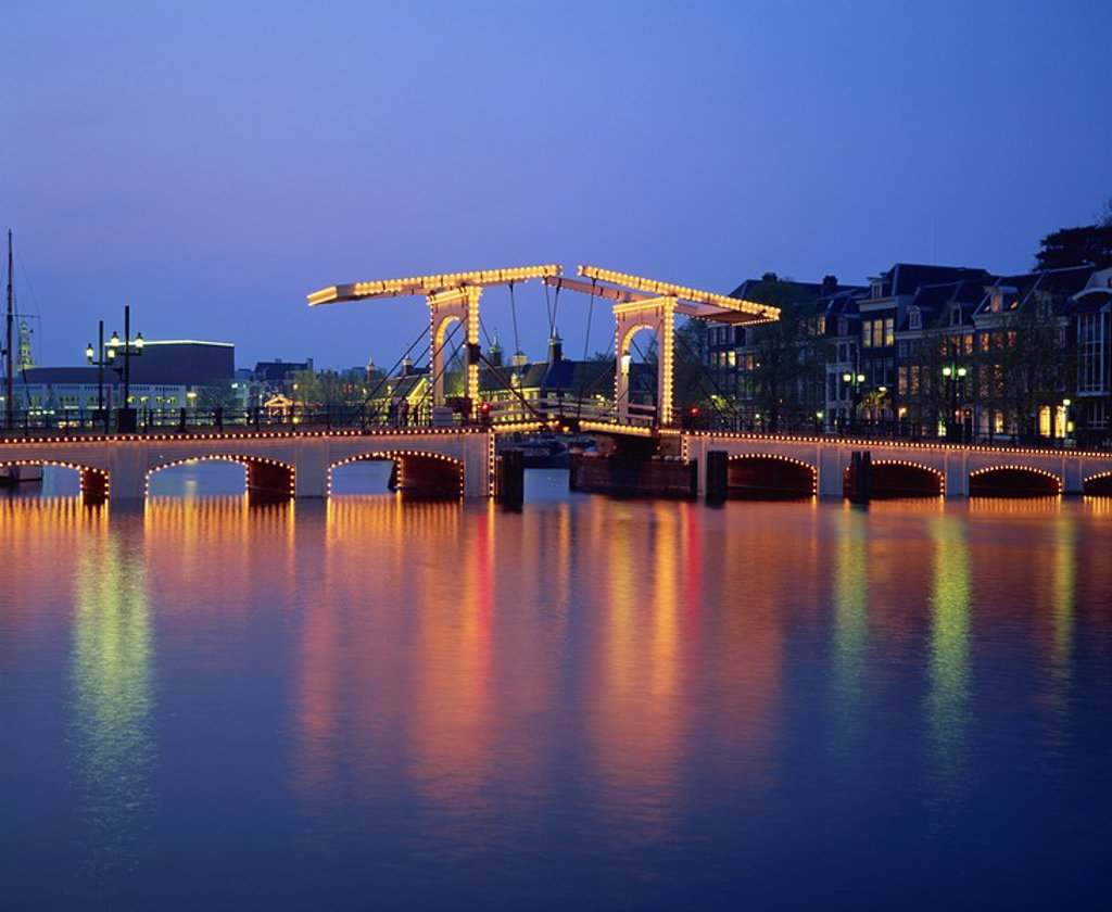 Lights on the Magere Brug Skinny Bridge, reflected in the canal in the evening in Amsterdam, Holland, Europe : Stock Photo