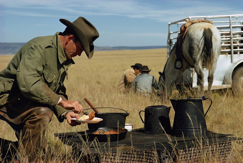 Stock Photo: 1890-27510 Cowboys eating breakfast in a field, New Mexico, United States of America, North America