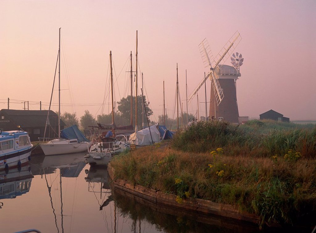 Horsey Wind Pump and boats moored on the Norfolk Broads at dawn, Norfolk, England, United Kingdom, Europe : Stock Photo