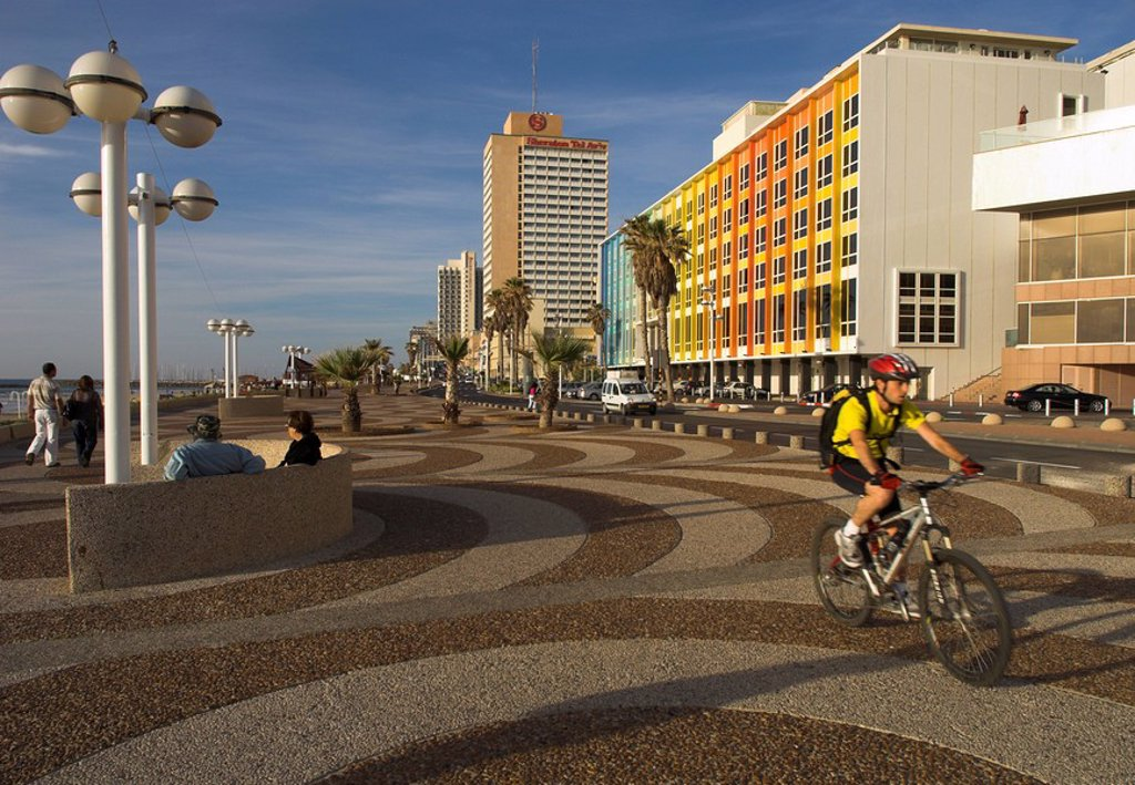 Cyclist on Jerusalem Beach Promenade with Dan hotel facade decorated by Yaaqov Agam in background, Tel Aviv, Israel, Middle East : Stock Photo