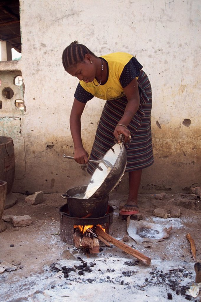 Portrait of a woman cooking outdoors over a small fire, Gambia, West Africa, Africa : Stock Photo