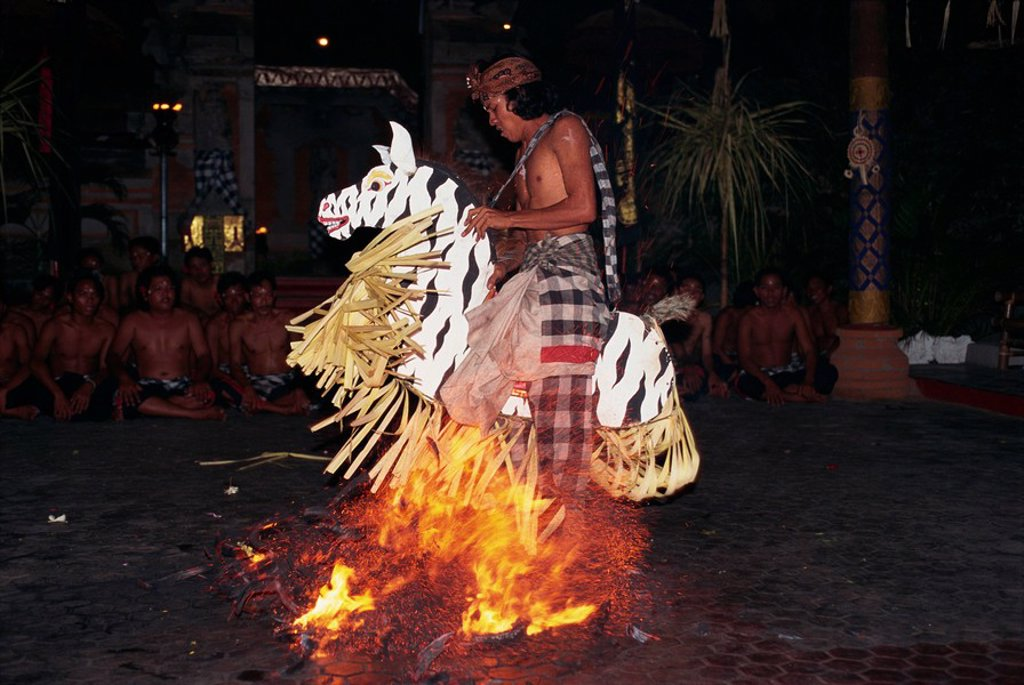 Stock Photo: 1890-32140 Portrait of a man riding a straw horse, walking on coals during fire dancing at night, Bali, Indonesia, Southeast Asia, Asia