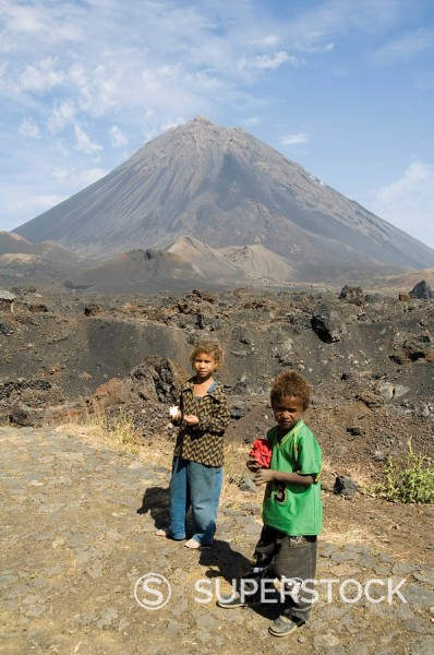 Child vendors selling souvenirs, with the Pico de Fogo volcano in the background, Fogo Fire, Cape Verde Islands, Africa : Stock Photo