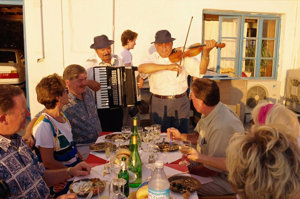 Tourists in open air restaurant being entertained by musicians including man playing accordion on Mykonos, Cyclades Islands, Greek Islands, Greece, Europe : Stock Photo