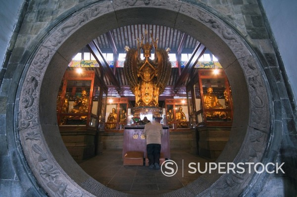 Stock Photo: 1890-46891 A woman praying in front of an arched entrance at West Garden Buddhist Temple, Suzhou, Jiangsu Province, China, Asia