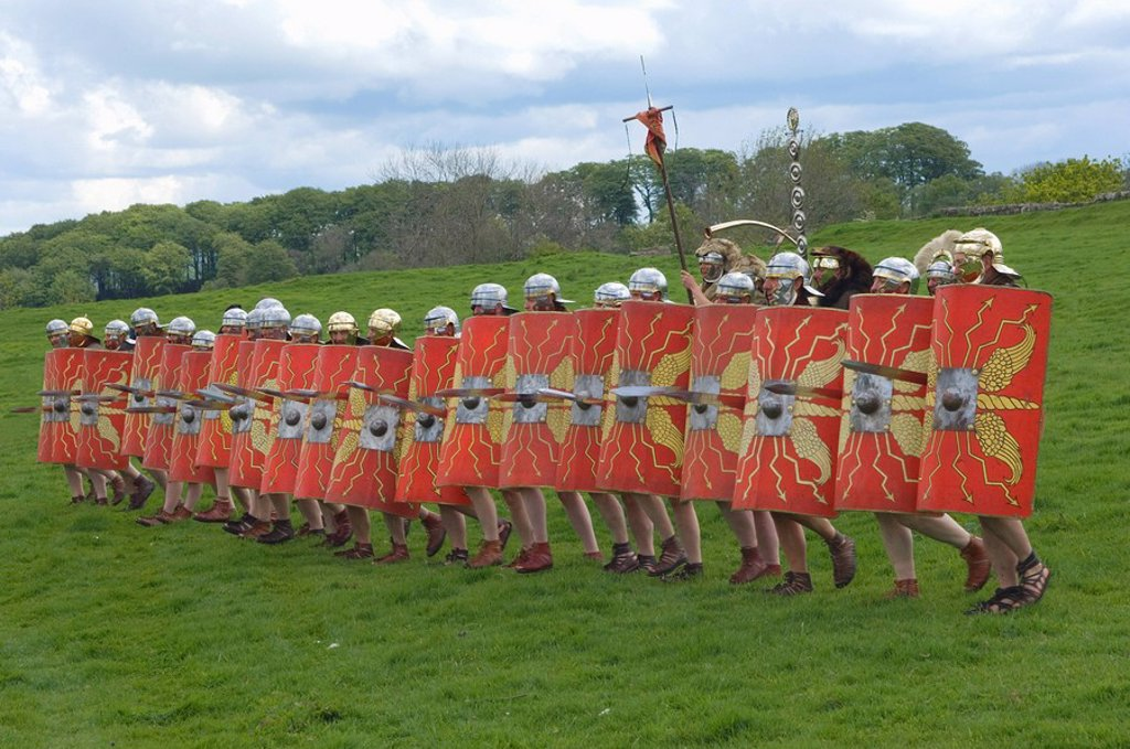 Roman soldiers of Ermine Street Guard, in line abreast with shields and stabbing swords, cavalry in support, Birdoswald Roman Fort, Hadrians Wall, Northumbria, England, United Kingdom, Europe : Stock Photo