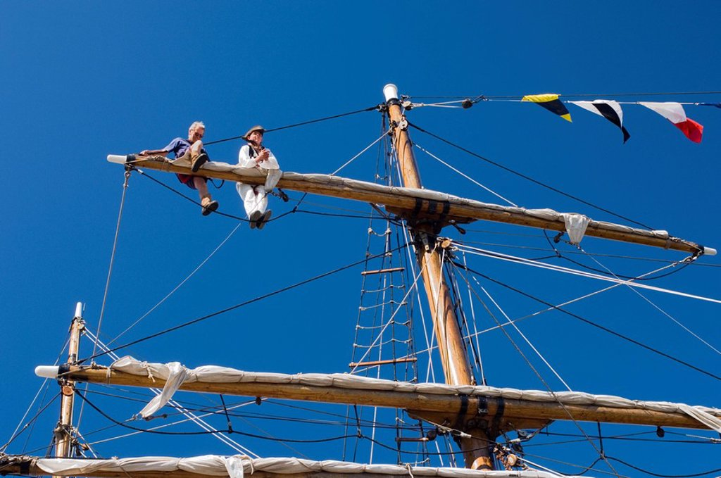 Detail of main mast of tall ship with two seamen on top yard securing sail, Whitehaven, Cumbria, England, United Kingdom, Europe : Stock Photo