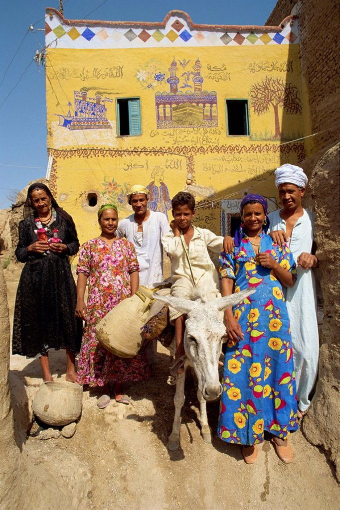 Portrait of a family, three generations, including a boy on a donkey, outside their painted house in the alabaster village of Dra Abul Naga, Egypt, North Africa, Africa : Stock Photo