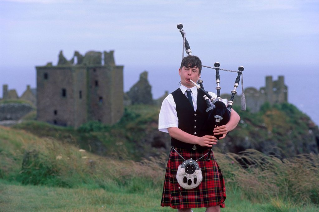 Stock Photo: 1890-55467 Piper playing, in front of Dunnotar Castle dating from the 14th century, near Stonehaven, Aberdeenshire, Scotland, United Kingdom, Europe