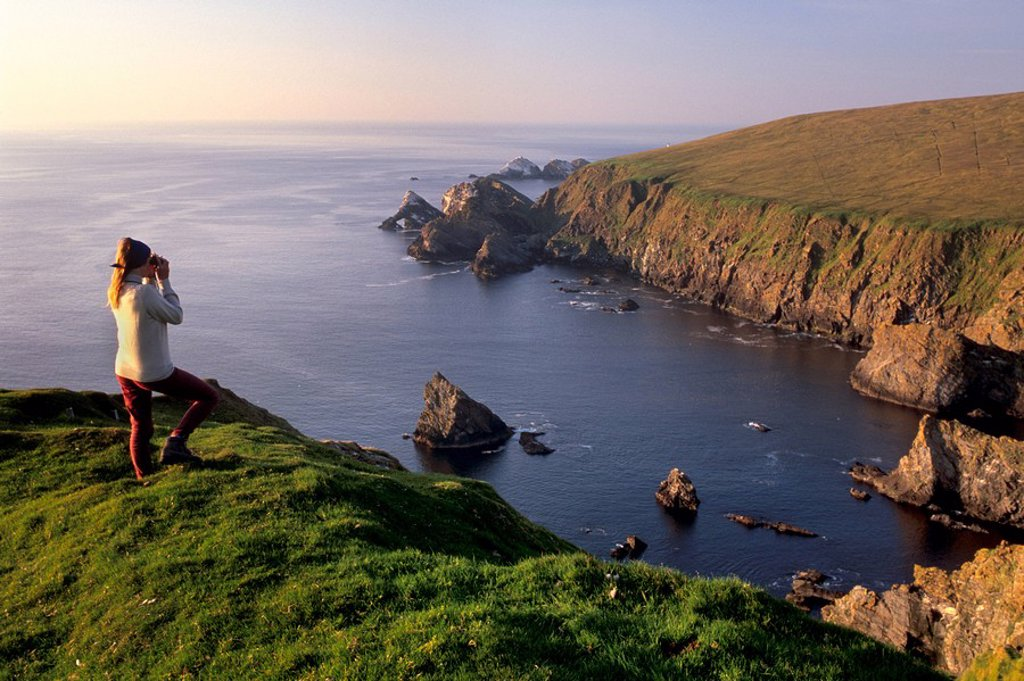 Stock Photo: 1890-55819 Birdwatching on cliffs of Hermaness Nature Reserve, looking north towards Vesta Skerry, Tipta Skerry gannetry, Muckle Flugga and its lighthouse in the distance, Unst, Shetland Islands, Scotland, United Kingdom, Europe