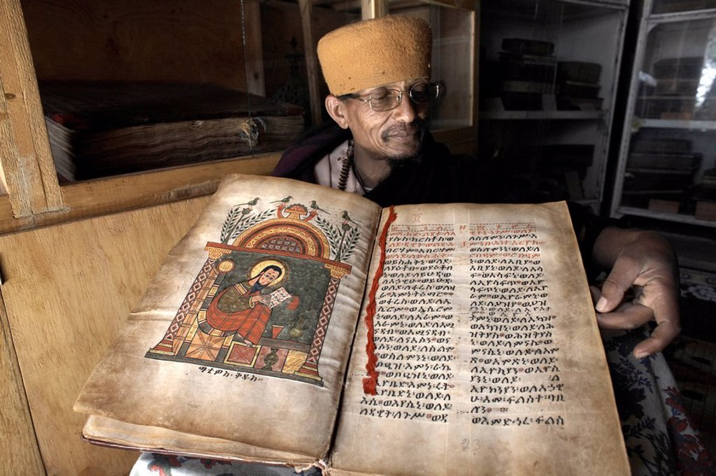 A priest goes through an ancient manuscript at the monastery of Kebran Gabriel, on an island on Lake Tana, Ethiopia, Africa : Stock Photo