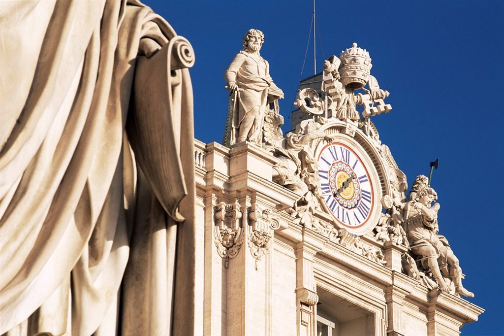 Clock adorning facade of St. Peter´s Basilica, with statue of St. Peter in front, Piazza San Pietro, St. Peters, Vatican City, Rome, Lazio, Italy, Europe : Stock Photo