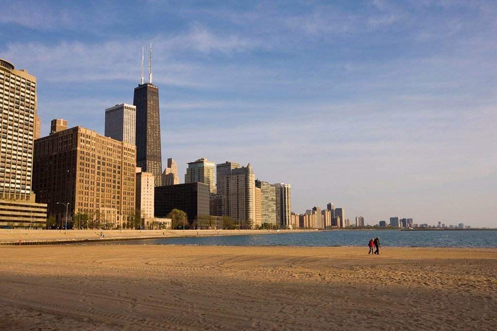 Walkers on Ohio Street Beach with city skyline behind, Chicago, Illinois, United States of America, North America : Stock Photo