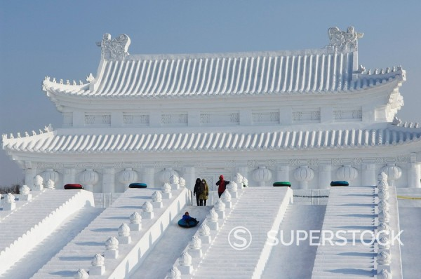 Stock Photo: 1890-79491 A boy slides down a giant replica sculpture of Beijing´s Forbidden City at the Snow and Ice Sculpture Festival on Sun Island Park, Harbin, Heilongjiang Province, Northeast China, China, Asia