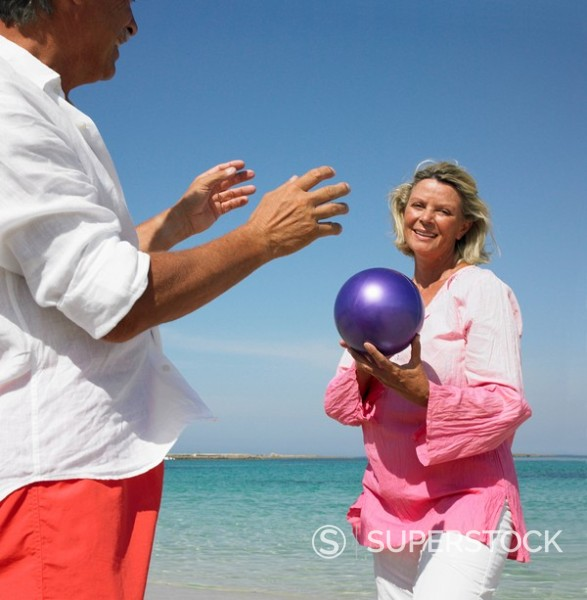 senior couple on beach playing with ball : Stock Photo