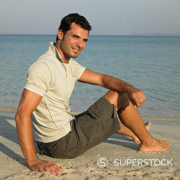 Stock Photo: 1890-84615 Man sitting on beach