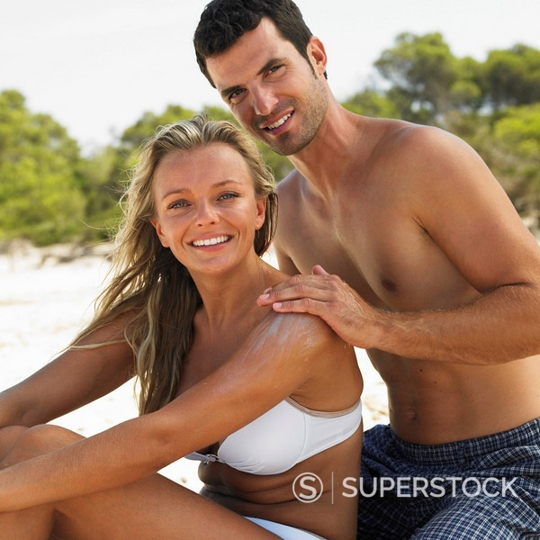 Stock Photo: 1890-84691 Man applying suncream to woman´s back on beach