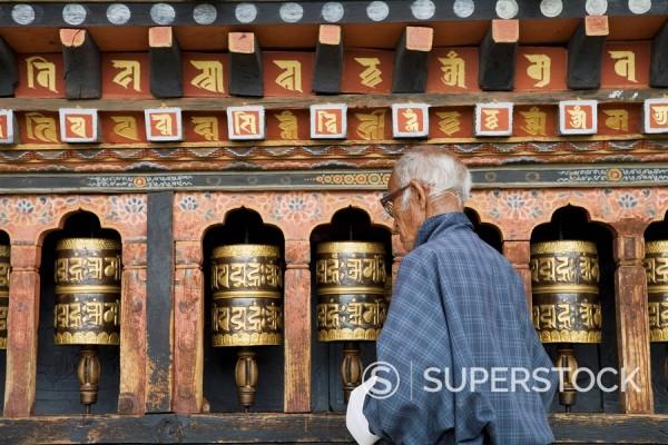 Old Bhutanese man turning prayer wheels in Buddhist temple, Thimphu, Bhutan, Asia : Stock Photo