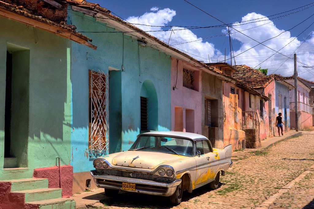 Classic American car parked on cobbled street outside brightly painted houses, Trinidad, Cuba, West Indies, Central America : Stock Photo