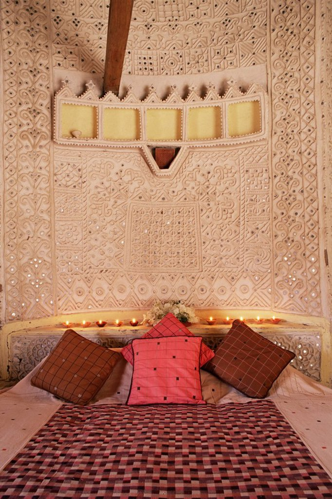 Raised mud reliefs inlaid with mirror on the walls of bedroom in modern home in traditional tribal Rabari round mud hut, Bunga style, near Ahmedabad, Gujarat state, India, Asia : Stock Photo