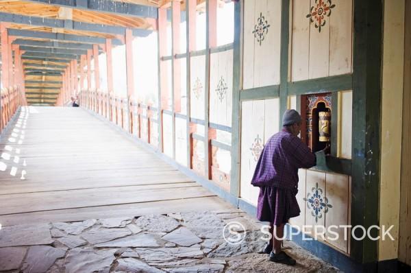 Stock Photo: 1890-97672 Local man spinning a prayer wheel, Punakha Dzong dating from 1637, Punakha, Bhutan, Asia
