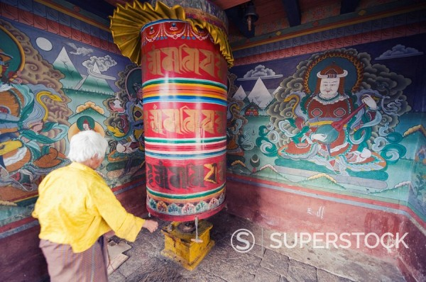 Stock Photo: 1890-97678 A woman spinning prayer wheel, Chimi Lhakhang dating from 1499, Temple of the Divine Madman Lama Drukpa Kunley, Punakha, Bhutan