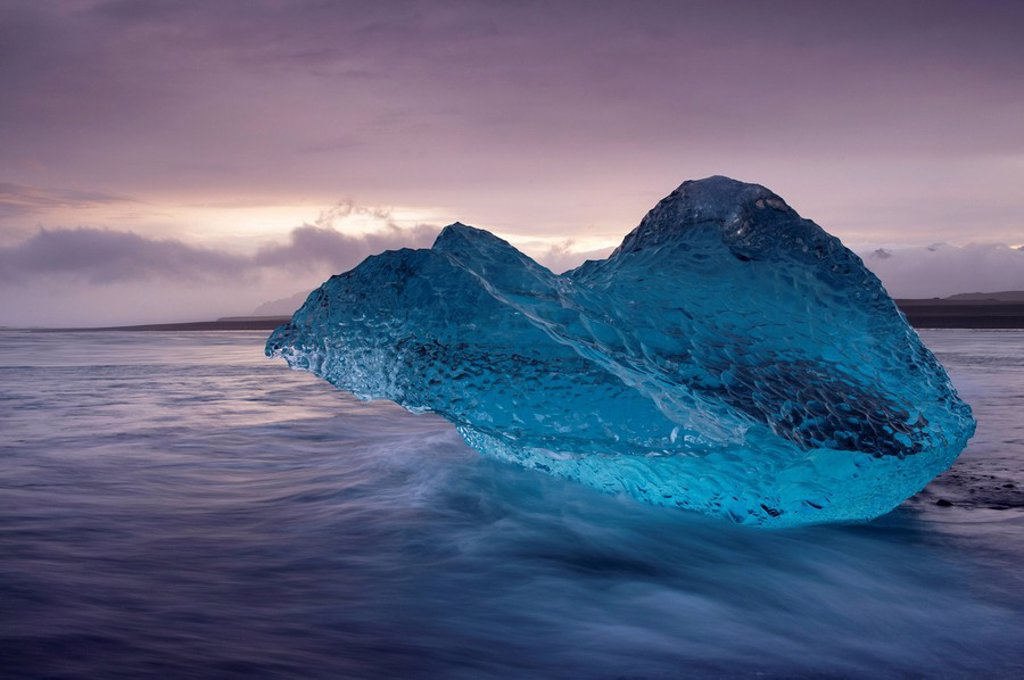 Translucent blue iceberg washed ashore on Breidamerkursandur black sands, near Jokulsarlon glacial lagoon, East Iceland, Polar Regions : Stock Photo