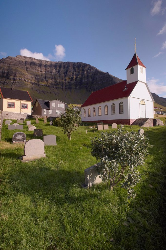 Church and village of Kunoy, located on the west coast of the island Kunoy, impressively surrounded by high mountains, Kunoy island, Nordoyar, Faroe Islands Faroes, Denmark, Europe : Stock Photo
