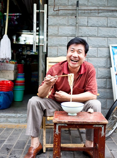 Stock Photo: 1891-249 Mature man eating noodles in front of a store, Shanghai, China