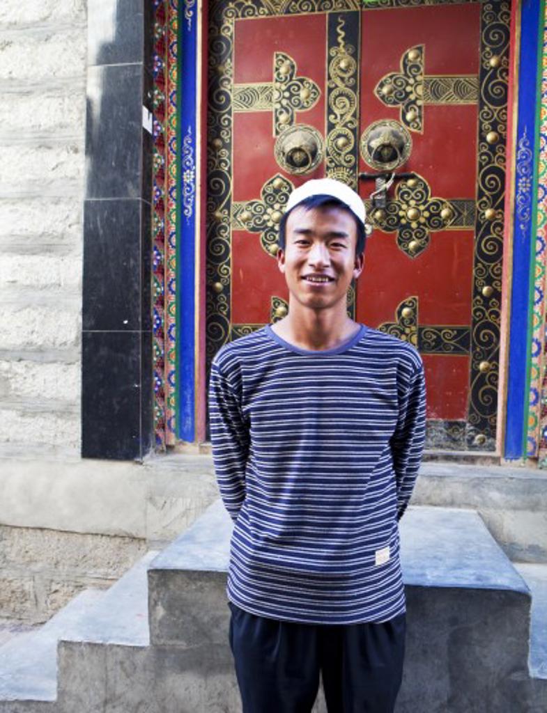 Man standing in front of a closed door, Tibet : Stock Photo