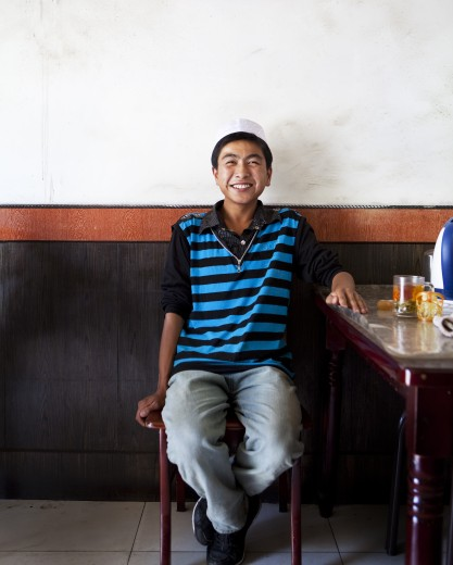 Teenage boy sitting on the stool and smiling, Tibet, : Stock Photo