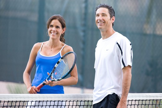 Young couple playing tennis in the court of a tourist resort : Stock Photo