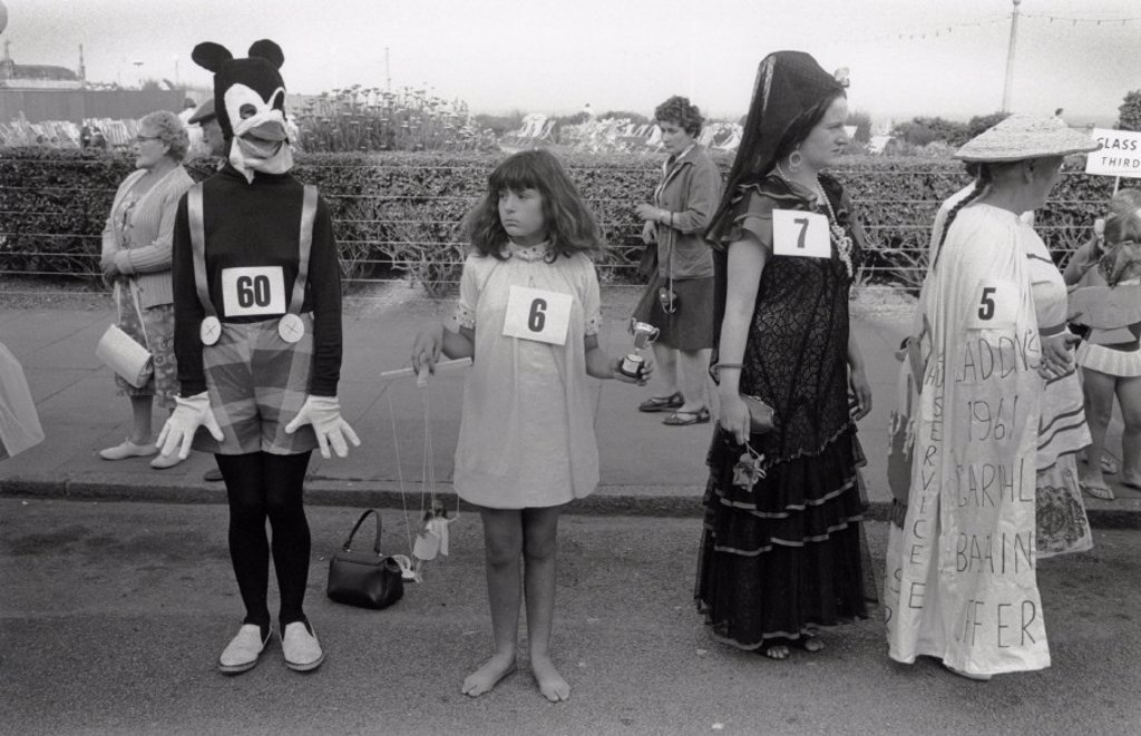 Stock Photo: 1895-13291 Children in fancy dress, standing in road at street carnival, 1968.