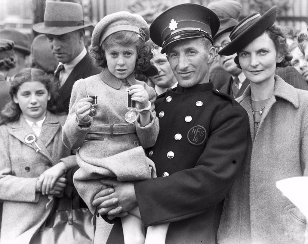 Stock Photo: 1895-17608 Fireman and his family with medal, Buckingham Palace, 8 May 1945
