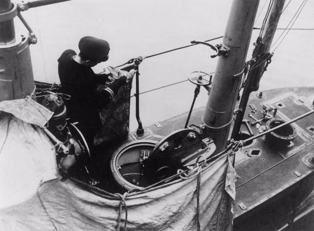 Officer of a submarine fixing a message to the leg of a carrier-pigeon, 1914-1918. : Stock Photo