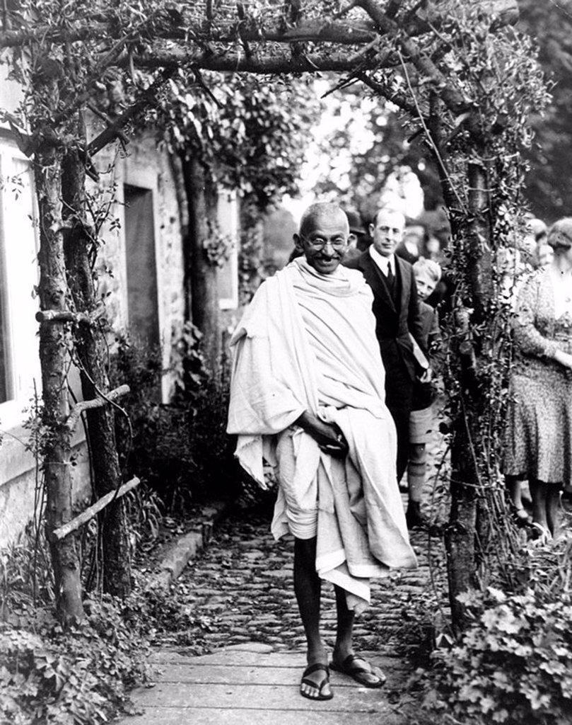 Mahatma Gandhi posing under a rustic arch, England, 1931 : Stock Photo