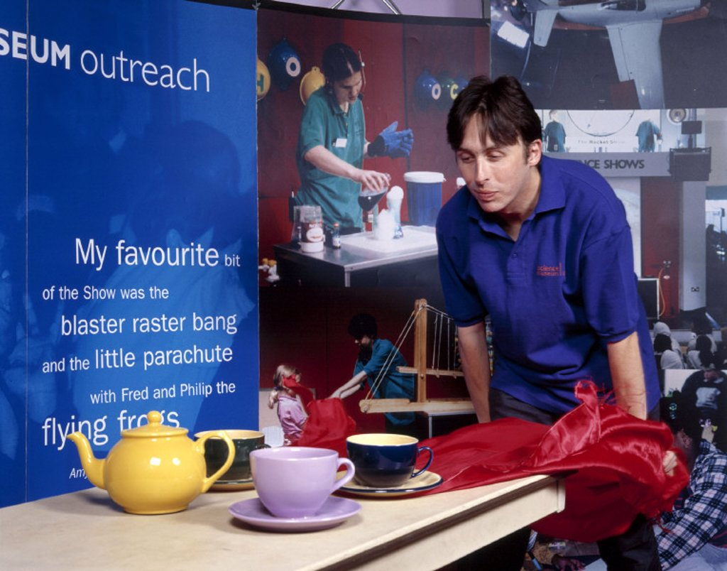 Pulling a tablecloth out from under a tea set, Science Museum, August 2001. : Stock Photo