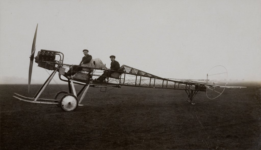 Stock Photo: 1895-24081 Two aviators sitting in an aeroplane with its skin and wings removed, c 1910s.