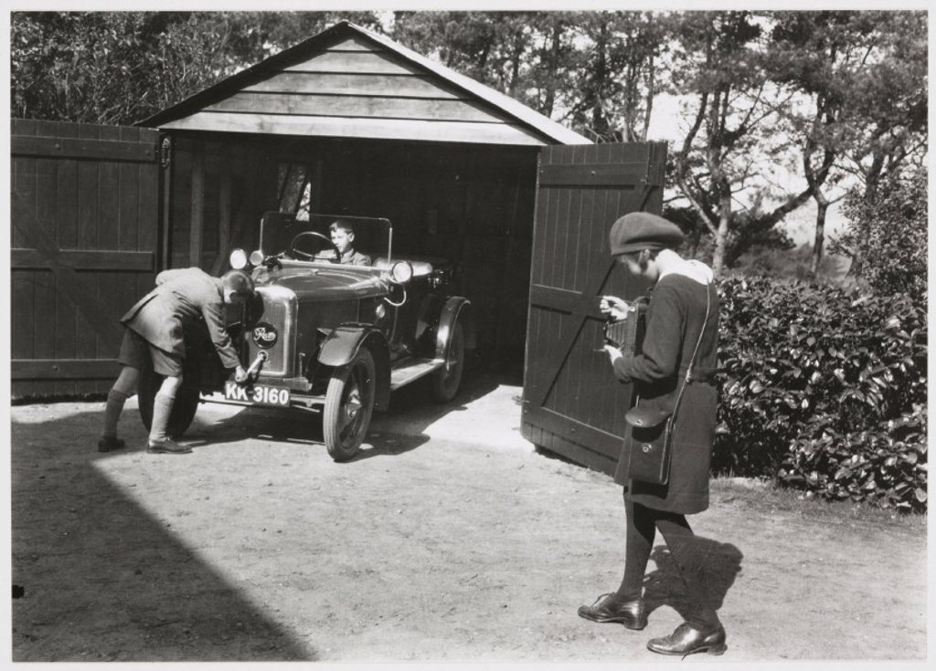 Stock Photo: 1895-29791 Girl photographing boys and car, c 1930