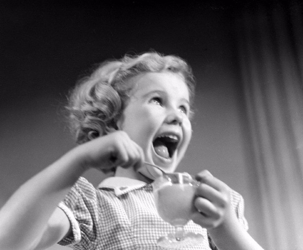 Laughing girl eating dessert, 1950 : Stock Photo