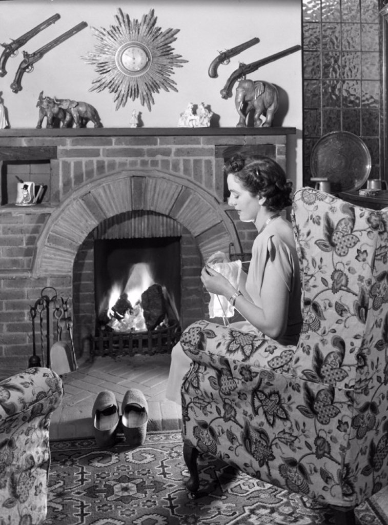Stock Photo: 1895-30344 Woman knitting by the fire, c 1950