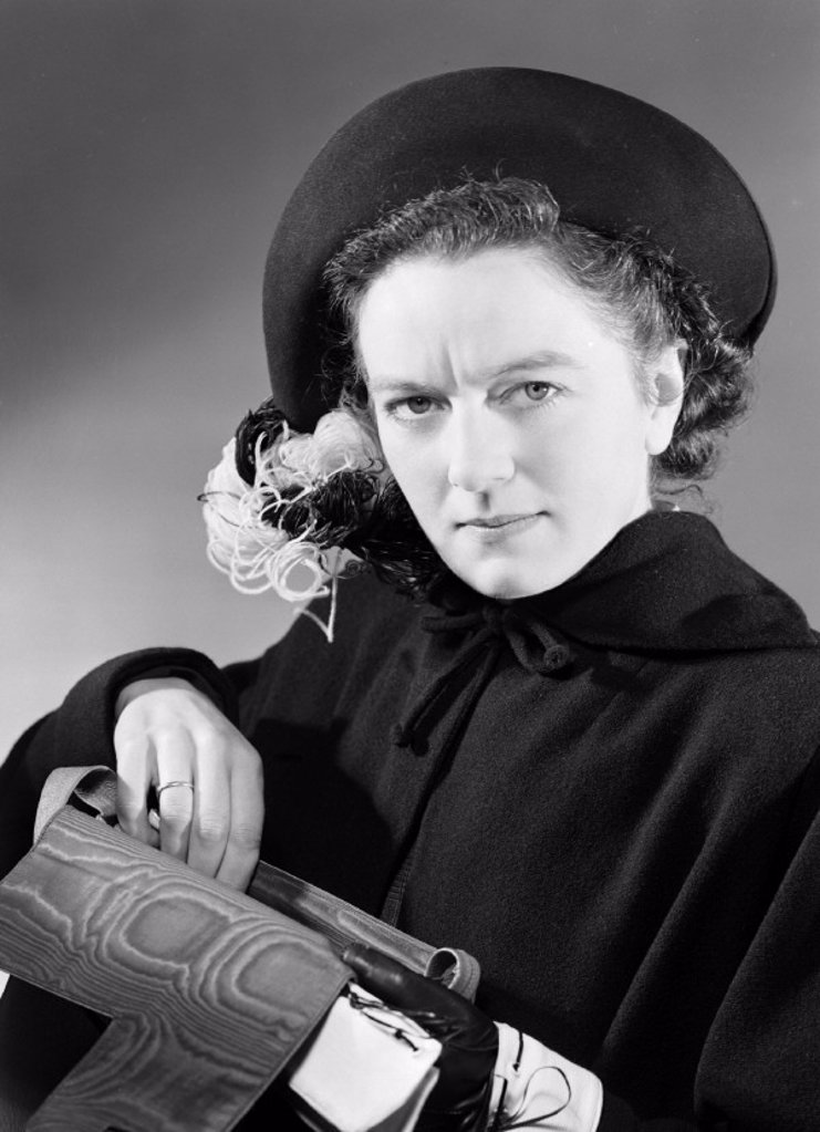 Woman reaching into her handbag, 1949 : Stock Photo