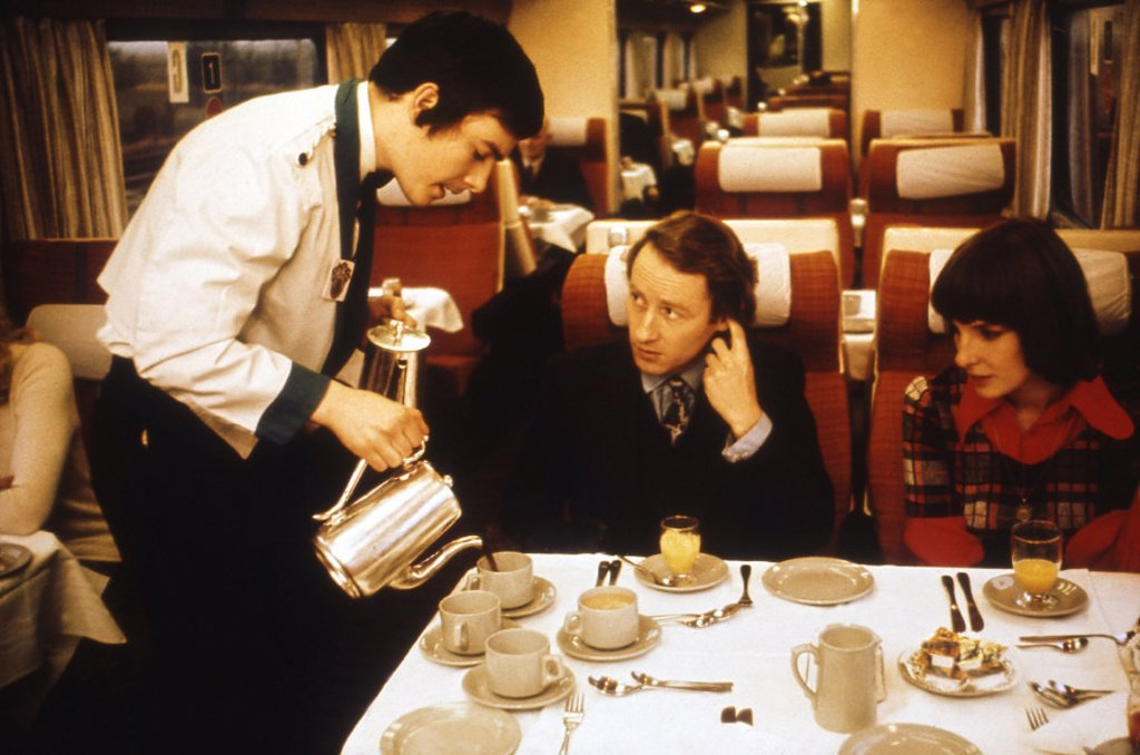 Stock Photo: 1895-33956 Steward serving coffee to a couple on the train, 1975-1985.