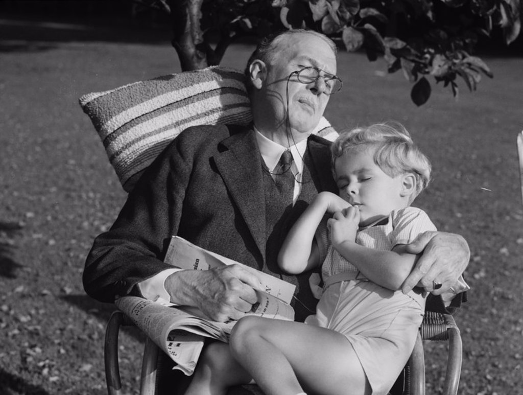 Stock Photo: 1895-40516 A boy and his grandfather in a chair in the garden, c 1930s