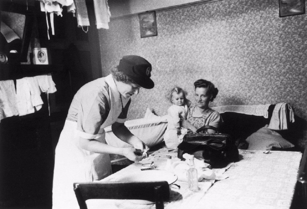 District nurse attending a sick child, November 1955. : Stock Photo