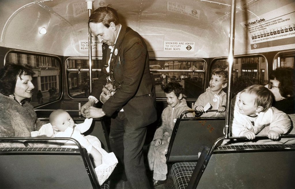 Stock Photo: 1895-43975 Bus conductor collecting a fare from a doll, 1982.
