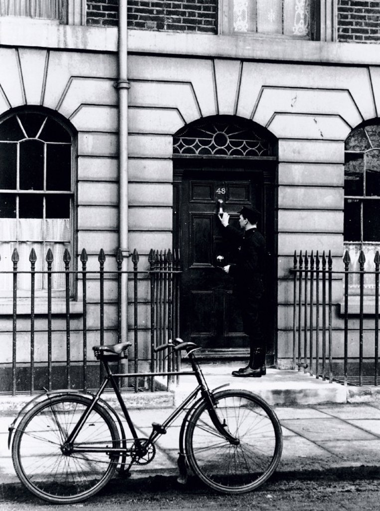 Postman delivering a telegram to an address in London, c 1930s. : Stock Photo