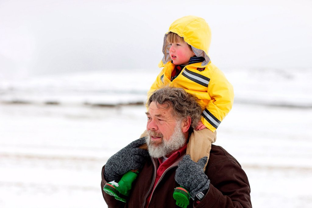 A portrait of a grandfather carrying his grandson on his sholders through the snow, Kamberg, KwaZulu_Natal, South Africa : Stock Photo